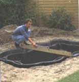 Проверка уровня садового пластикового пруда